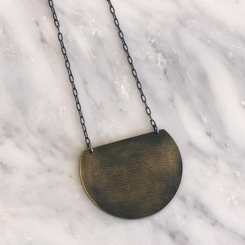 This Half Moon Necklace from Queens Metal is a flat, moon-shaped necklace in blackened gold with an intricate, wavy design.