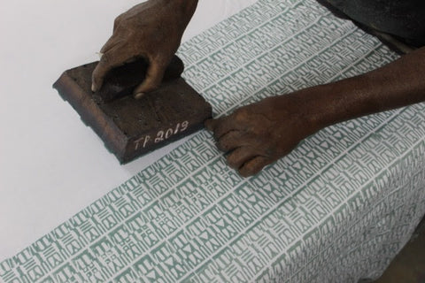 An artisan hand block printing fabric for Passion Lilie's clothes made in India.