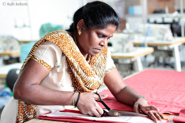 A fair trade artisan cuts fabric.