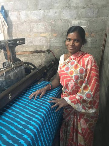 One of Passion Lilie's fair trade artisans from India, pictured here smiling while looming fabric.