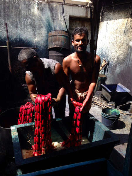 Two Indian handloom weavers dyeing the threads that will be used for handloom weaving.