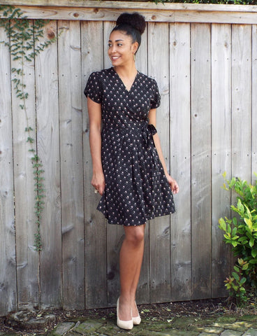 Black with a subtle gray-and-peach poppies with polka dots design, this Fall Poppies Wrap Dress from Passion Lilie has short sleeves and pockets.