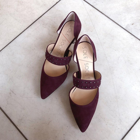The Drisela is a pair of pointed toe pumps, shown here in a rich burgundy suede with silver metallic studs on the top strap.
