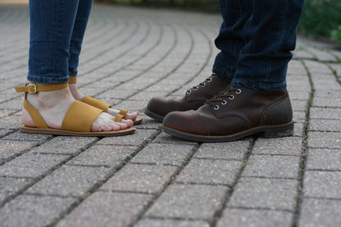 A fashionable yet comfortable pair of yellow women's sandals next to a sturdy and stylish pair of men's boots.
