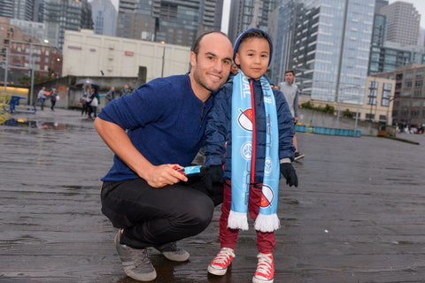 Landon Donovan posing with child wearing scarf