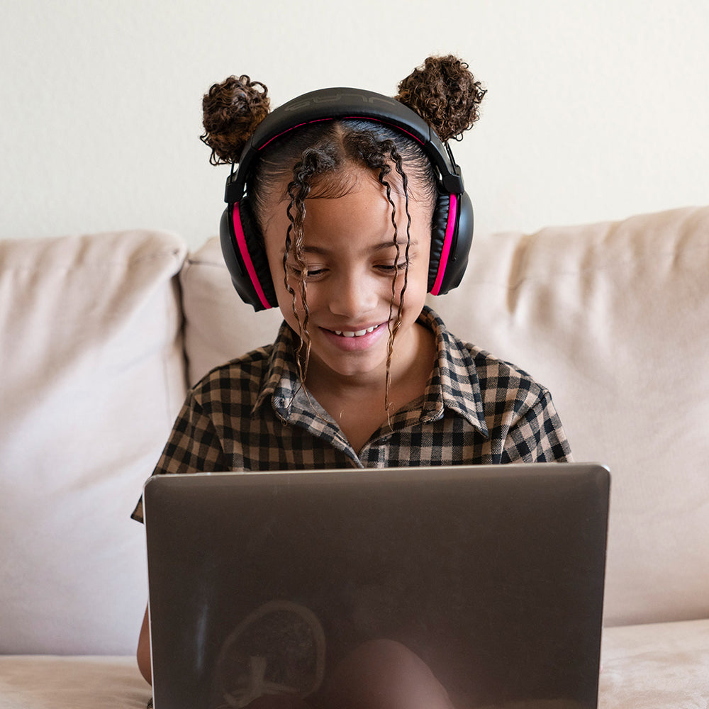 Girl at laptop wearing JBuddies Pro Wireless Over-Ear Headphones in Pink