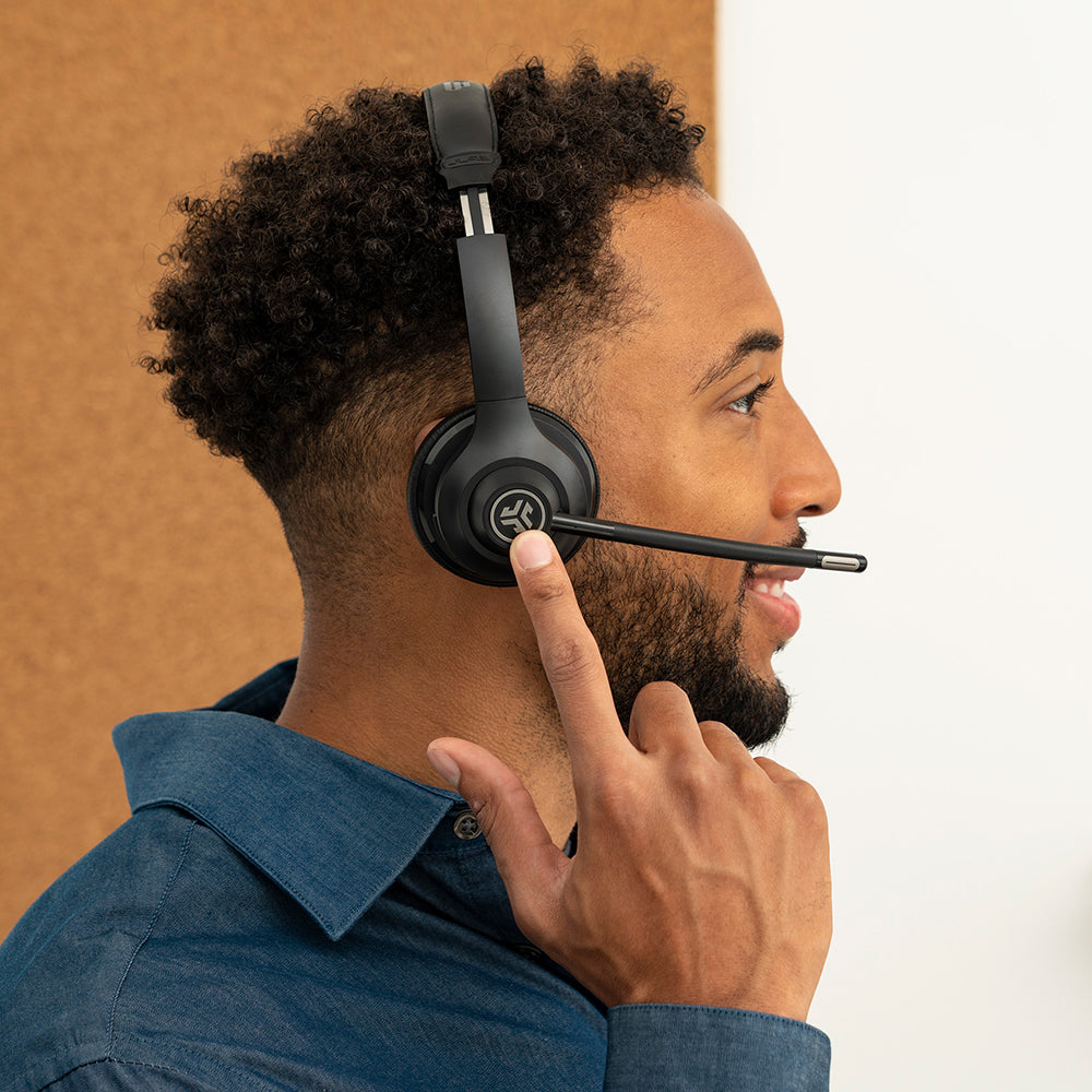 Man wearing GO Work Wireless On-Ear Headset and reaching for controls on earcup