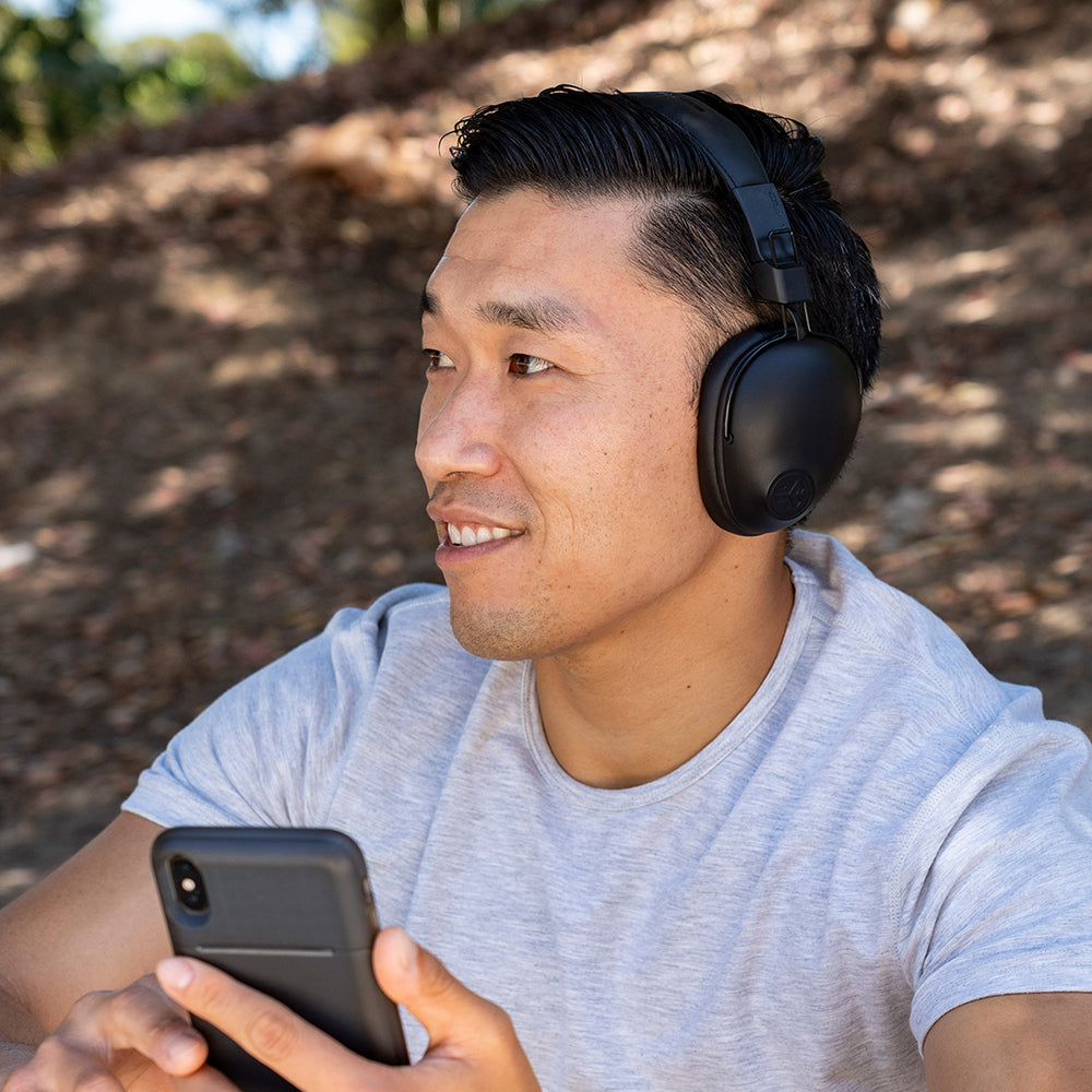 Man som bär svart Studio Pro Wireless Over-Ear hörlurar och mobiltelefon