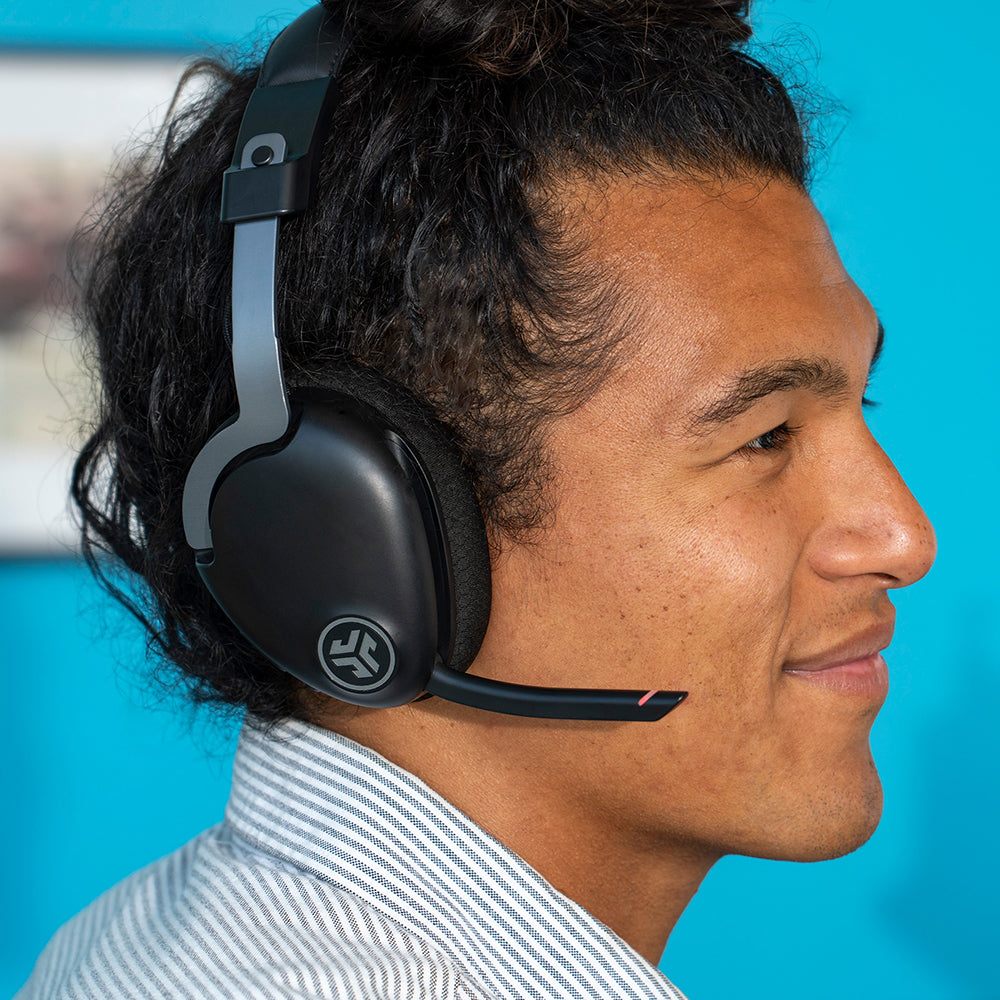 Man wearing JBuds Work Wireless Over-Ear Headset with boom mic flipped down and red quick mute indicator on
