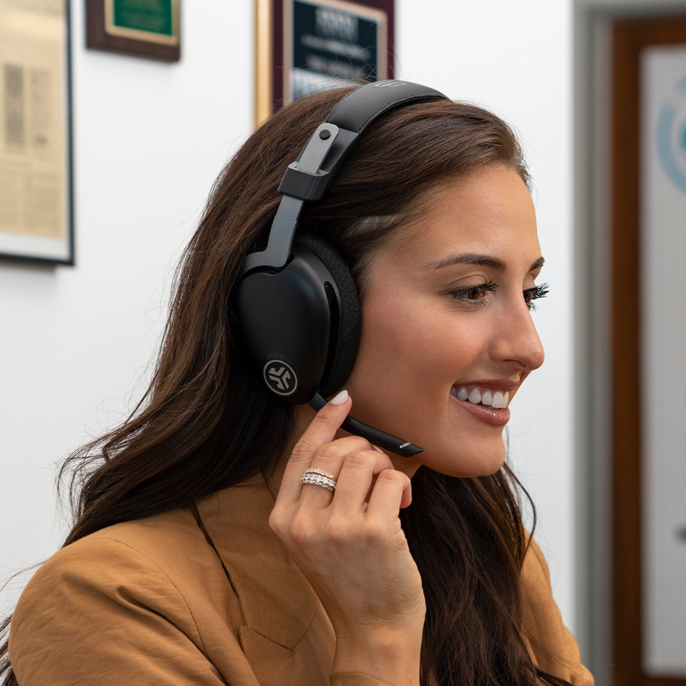 Woman wearing JBuds Work Wireless Over-Ear Headset with boom microphone rotated down for phone call