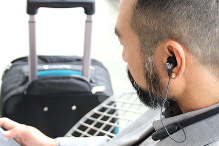 Traveling Businessman Wearing Epic Executive Earbuds