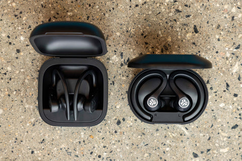 JBuds Air earbuds in case next to Powerbeats Pro