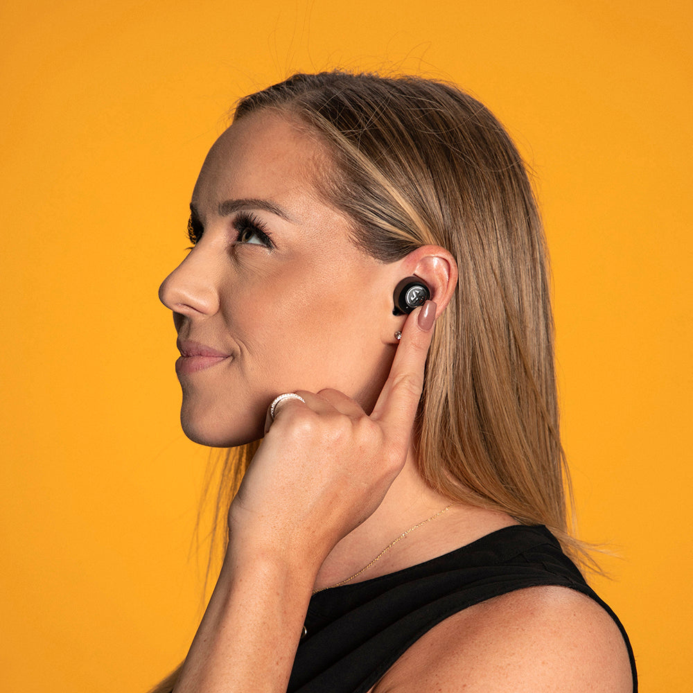 Woman wearing JBuds Air ANC True Wireless Earbuds and using touch sensors