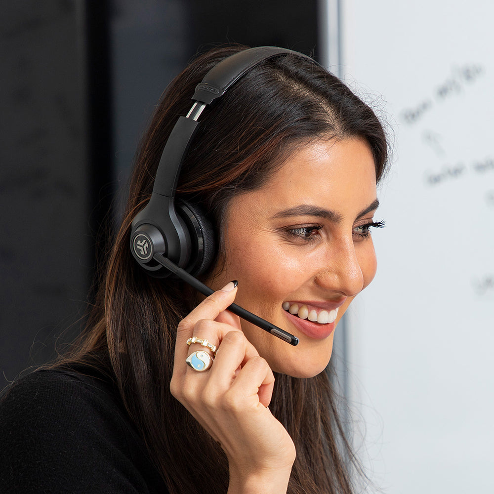 Woman wearing GO Work Wireless On-Ear Headset and touching boom microphone