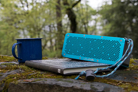 Blue Crasher XL Bluetooth Speaker Next to Book and Mug in Forest