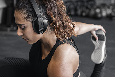 Mujer estirando en el gimnasio usando Flex Sport Wireless Bluetooth Headphones