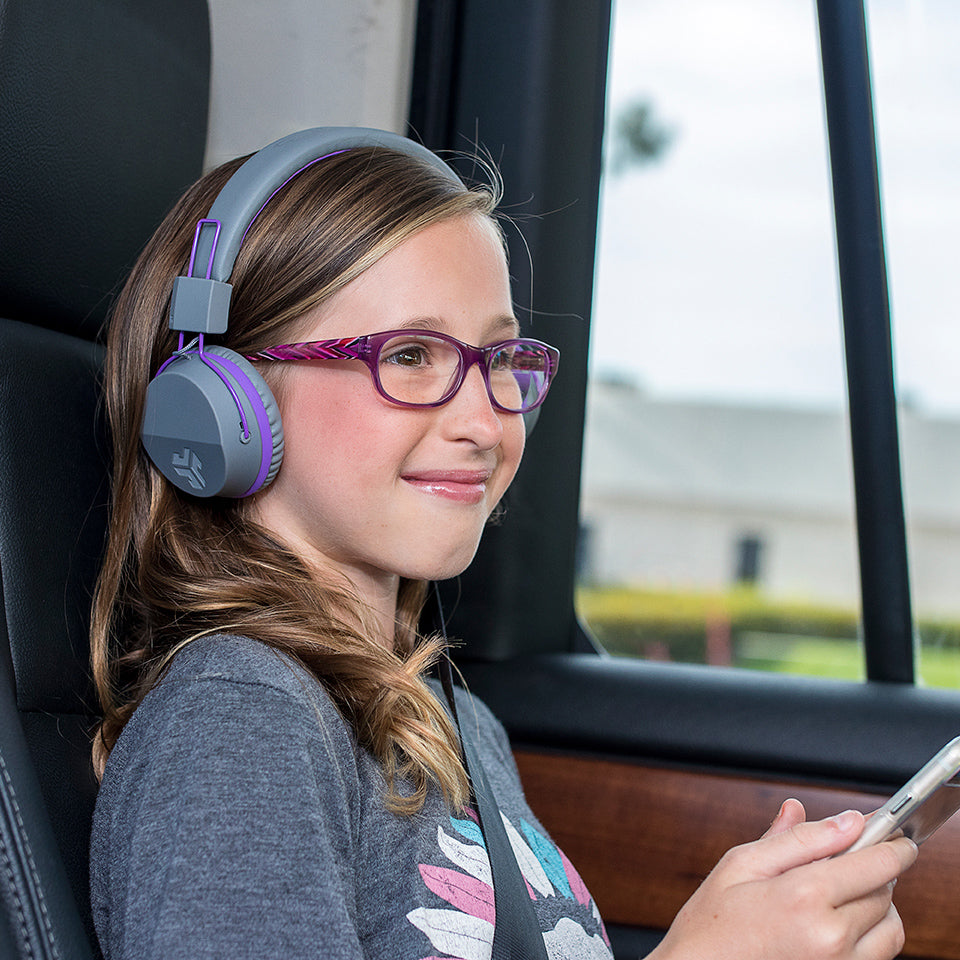 Girl wearing JBuddies Studio Bluetooth On-Ear Headphones in Purple