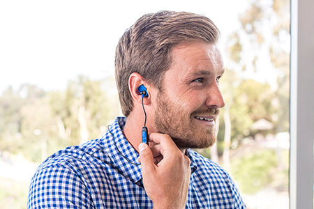 Kerl trägt Metal Bluetooth Rugged Earbuds in Blau