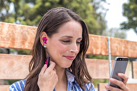 Woman wearing pink Metal Wireless earbuds holding phone and touching touch controls