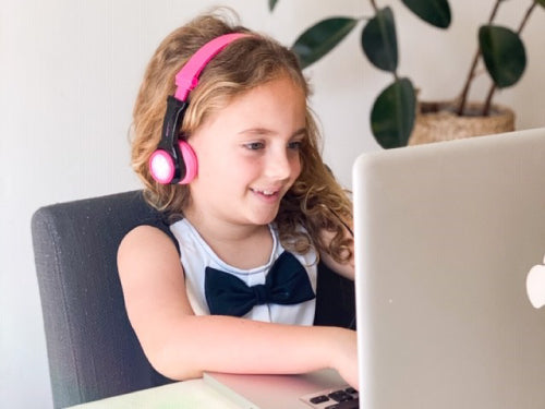 child with Jbuddies folding headphones