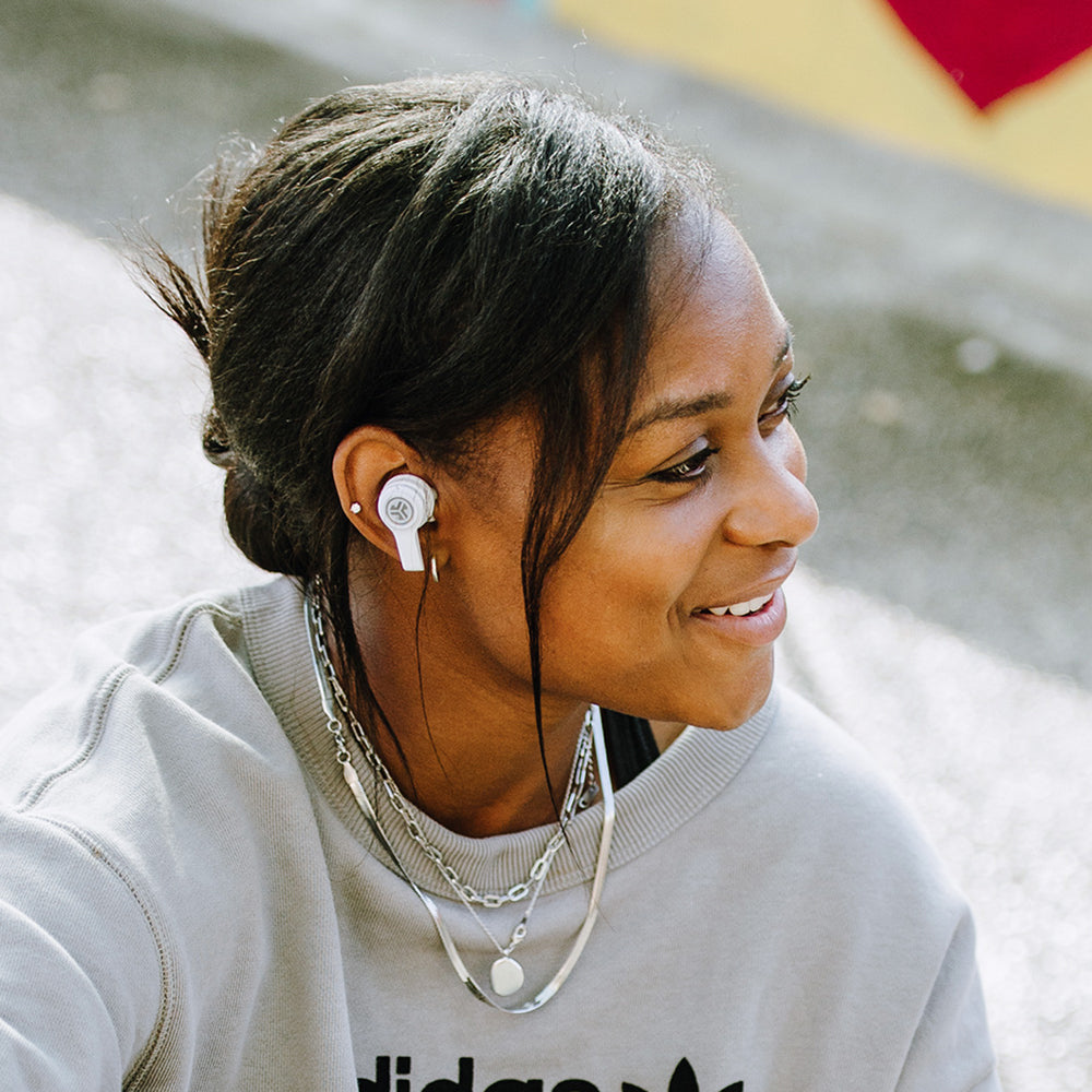 Side profile of woman wearing white JBuds Air Executive True Wireless Earbuds