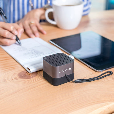 Gunmetal Crasher Micro Speaker on Desk Next to Woman Writing