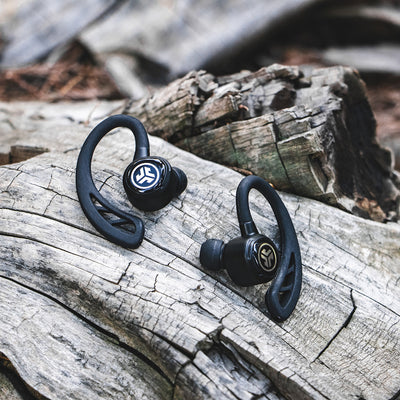 Close-up of Black Epic Air Elite True Wireless Earbuds on Log