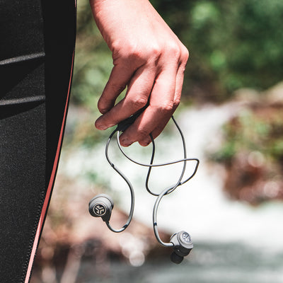 Man Holding Gray Epic Sport Wireless Earbuds