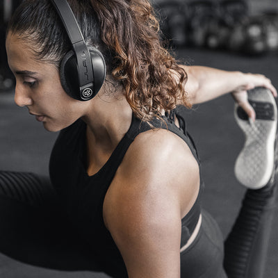 Woman Stretching in Gym Wearing Flex Sport Wireless Bluetooth Headphones
