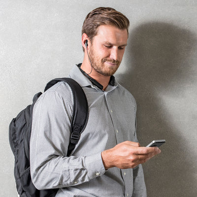 Man with Backpack Holding Cellphone Wearing Gravity Bluetooth Neckband Adapter and Earbuds