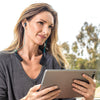 Woman Holding Tablet and Wearing Gravity Bluetooth Neckband Adapter and Earbuds