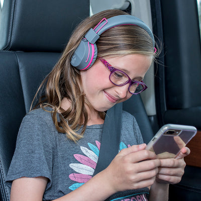 Image of girl wearing the JBuddies Studio Bluetooth Over Ear Folding Kids Heaphones in Pink