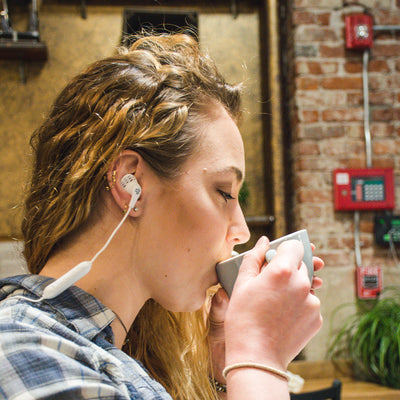 Girl wearing JBuds Pro Bluetooth Signature Earbuds in white