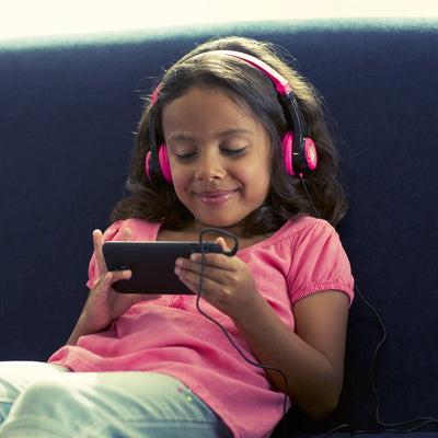 Girl Laying on Couch Wearing Pink and Black JBuddies Headphones