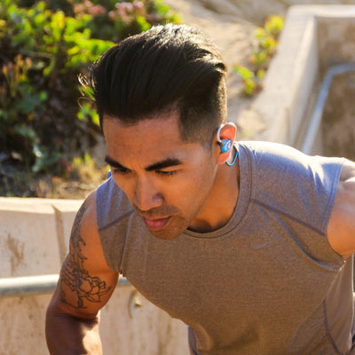 Man Running with Blue and Gray Epic2 Wireless Earbud