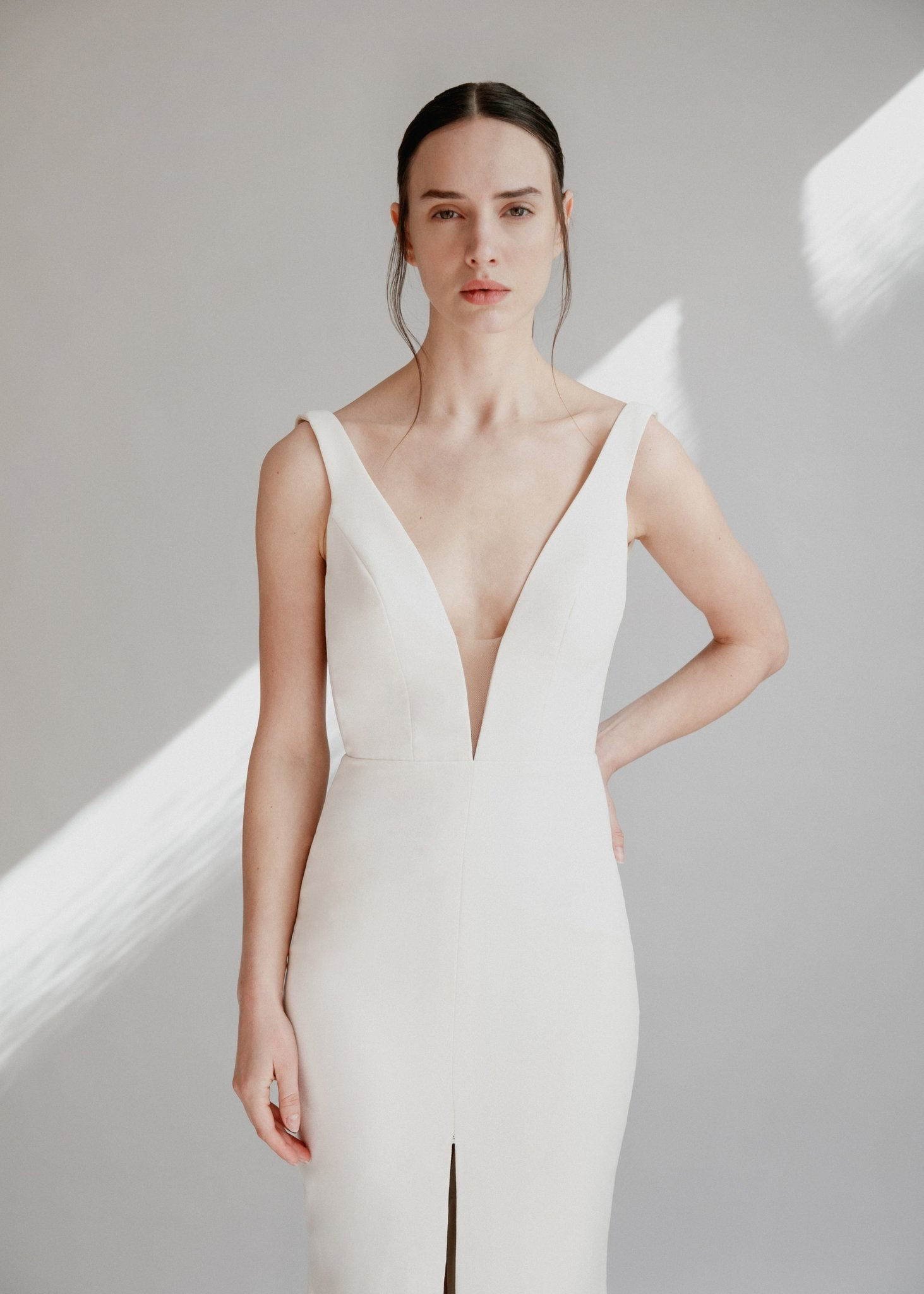 Simple and minimalist wedding dress in full crepe with a low back, deep v front, and a centre slit