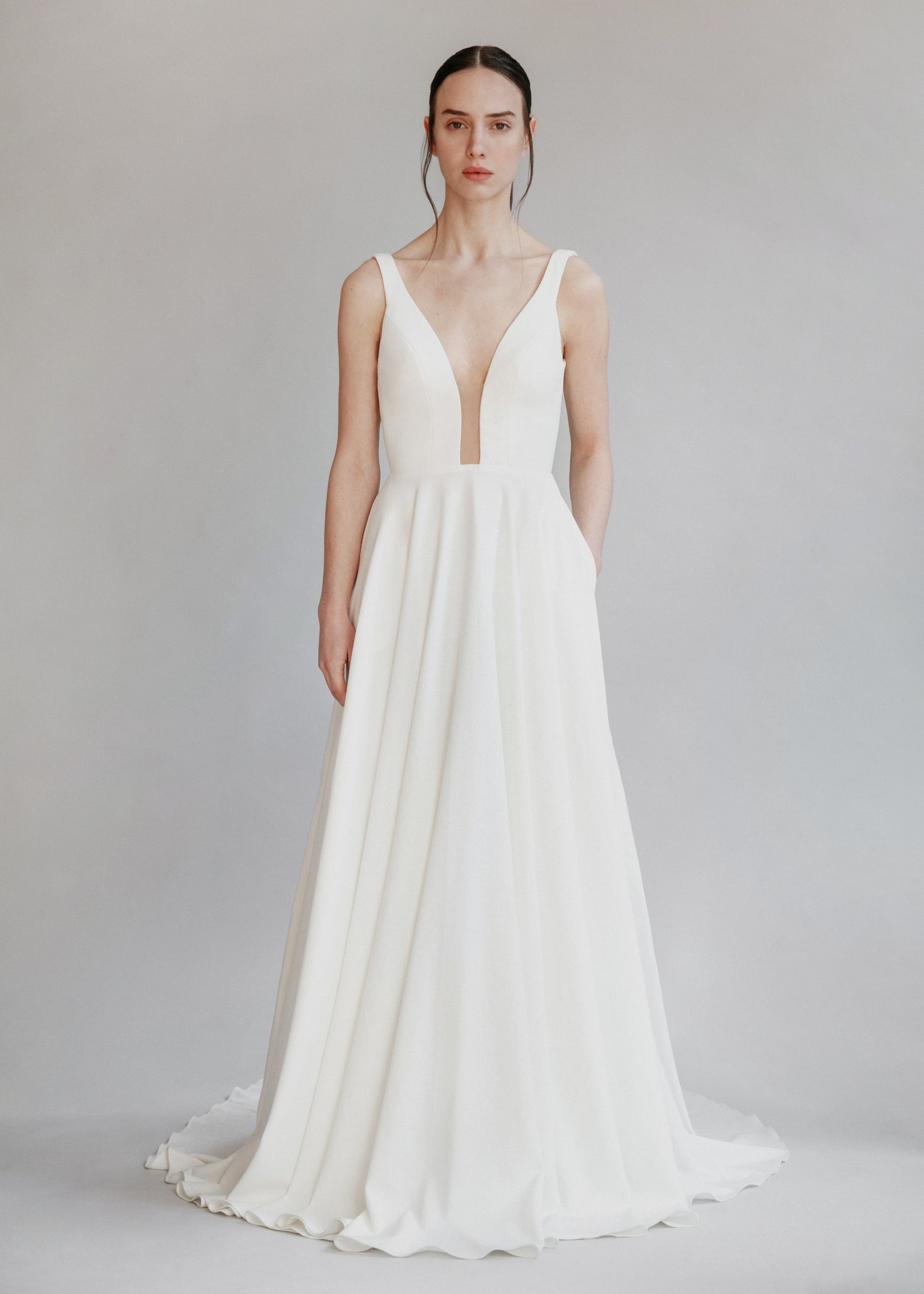 Simple crepe wedding dress with a plunging neckline, open back, and hidden pockets