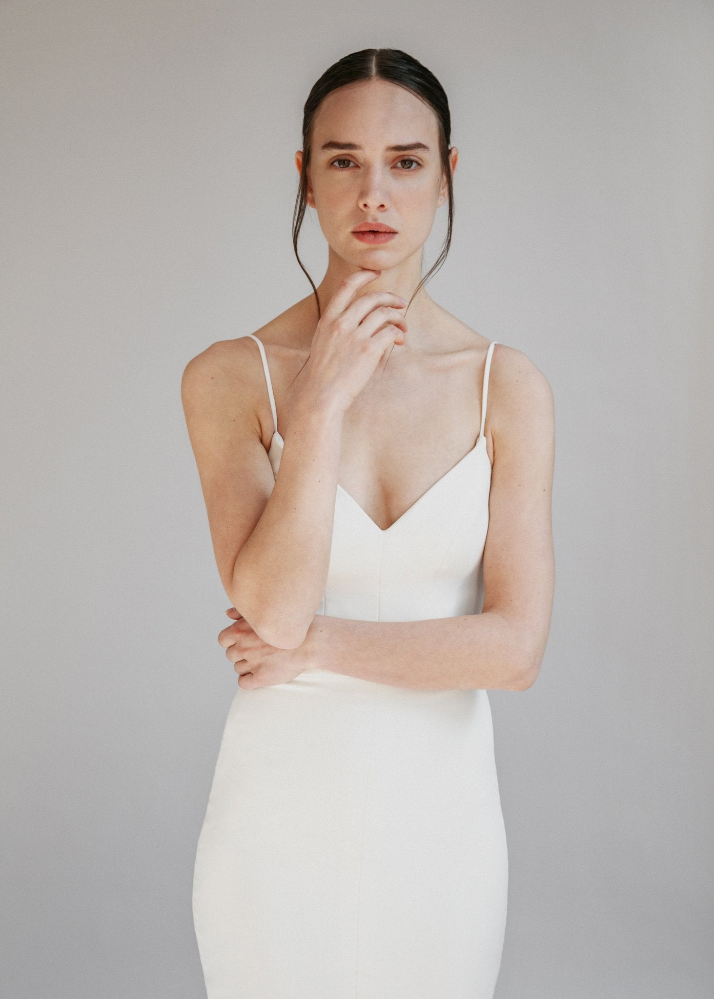 Simple crepe mermaid wedding dress with a low back, spaghetti straps, and a centre slit skirt