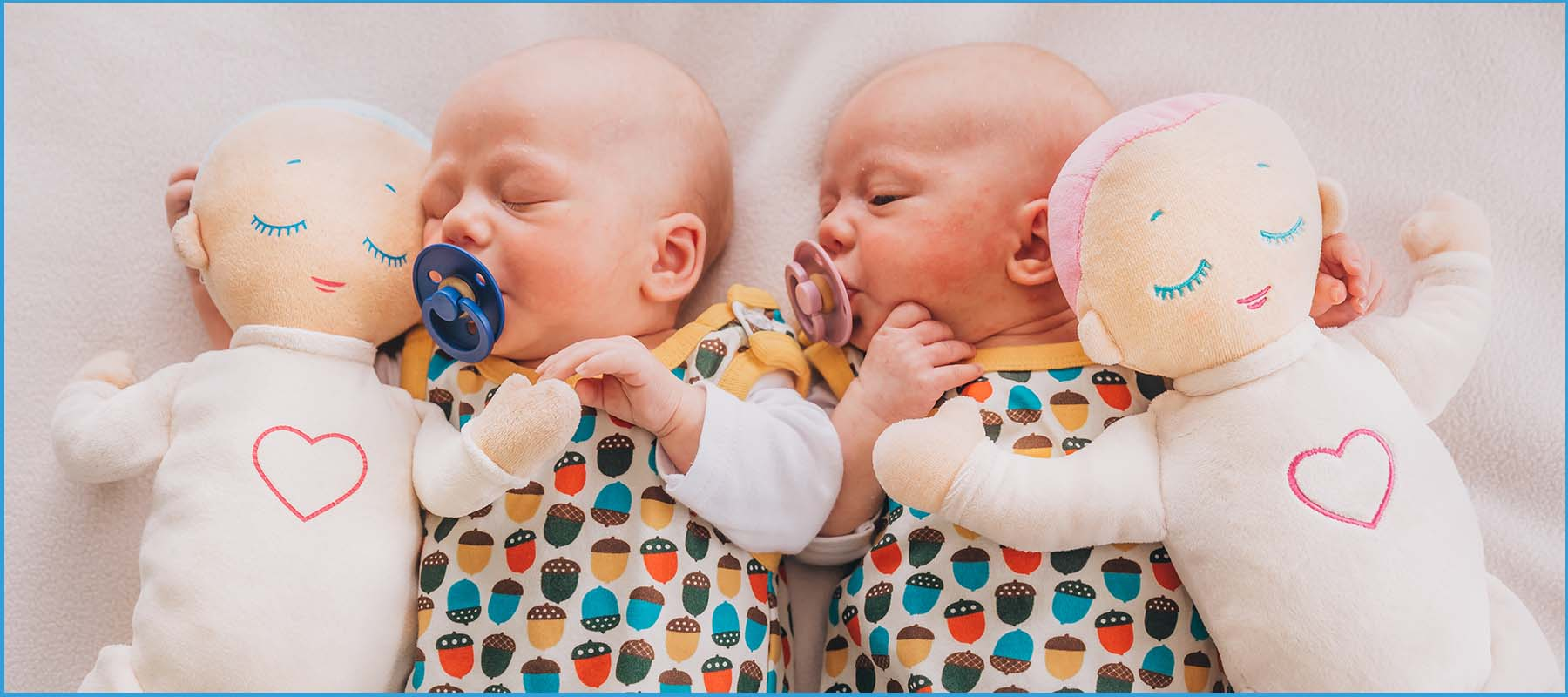 two twin babies holding Lulla Dolls