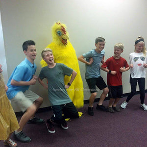 Children Clucking next to a Big Yellow Chicken