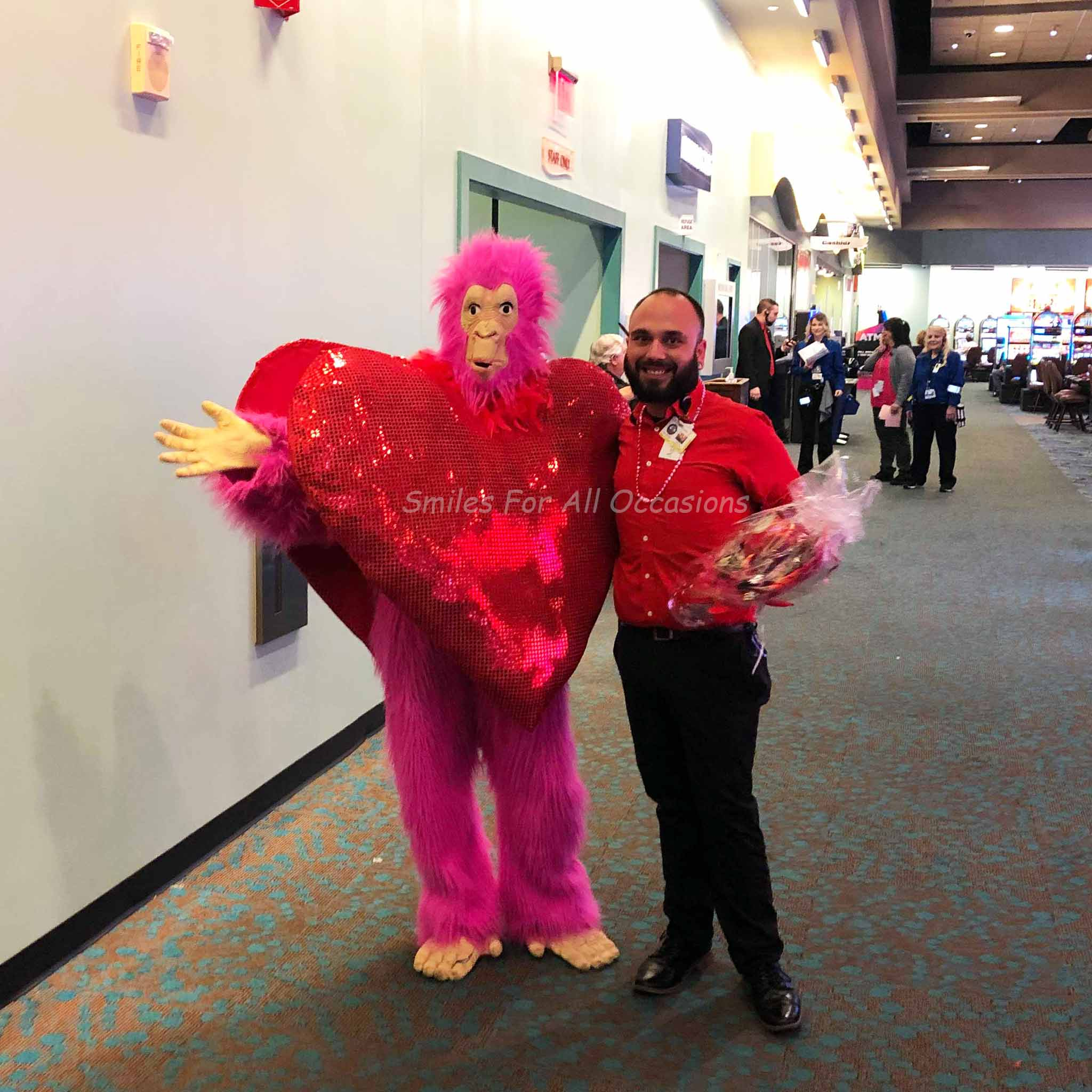 Pink Gorilla with Large Red Heart on Chest Standing with a Man at Casino