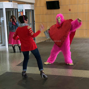Pink Gorilla with Large Red Heart on Chest Dancing with a Woman