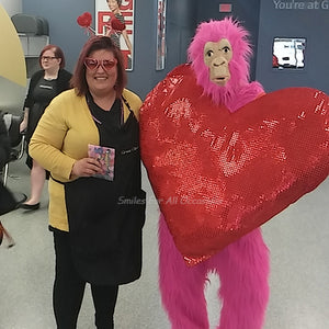 Pink Gorilla with Large Red Heart on Chest Standing with a Woman