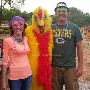 Man and Woman with Birthday Hat and Glasses Next to Chicken Costume
