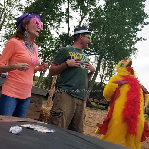 Man and Woman with Birthday Hat and Glasses Clucking Next to Chicken Costume