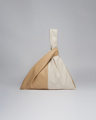 A bag with tan and beige panels whose handles knot through each other as a closure.