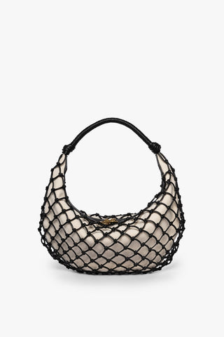 A small beige bag with black fishnetting around the outside of it and a circular top handle.
