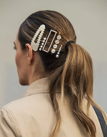 A woman with her back to the camera. In her brown hair are various pearl and gold hair accessories.