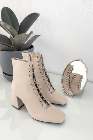 A pair of lace-up light beige boots with thick, short heels.