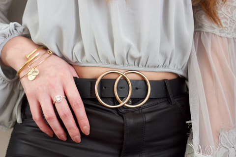 A close shot of a woman's midriff. She is wearing a grey cropped blouse and black leather pants with a thick, black belt that has two gold circles for the buckle. She has gold jewelry on the hand with its thumb hooked over her belt.